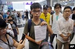 Hong Kong pro-democracy activist Joshua Wong, center, shows the letter from Thailand Immigration office after arriving at Hong Kong airport from Bangkok, Oct. 5, 2016.