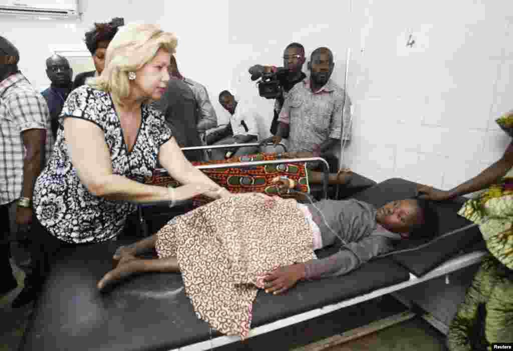 Ivorian President Alassane Ouattara's wife Dominique visits people injured in a stampede that occurred after a New Year's Eve fireworks display in Abidjan, January 1, 2013.
