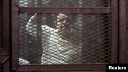 FILE - A Muslim Brotherhood supporter convicted of playing a role in the killings of 16 policemen in August 2013, stands behind bars during the trial in Cairo, Egypt, Feb. 2, 2015.