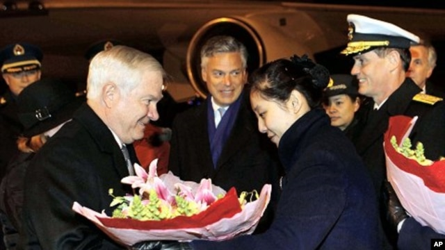 U.S. Secretary of Defense Robert Gates (L) receives flowers as he arrives at Beijing International Airport to start his four-day visit to China, 09 Jan 2011