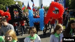 """People take part in a procession during celebrations marking the fourth anniversary of self-declared independence in Donetsk, Ukraine May 11, 2018. Translated, the balloons read """"DNR,"""" for the Donetsk People's Republic."""