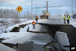 Workers inspect an off-ramp that collapsed during a morning earthquake, Nov. 30, 2018, in Anchorage, Alaska.