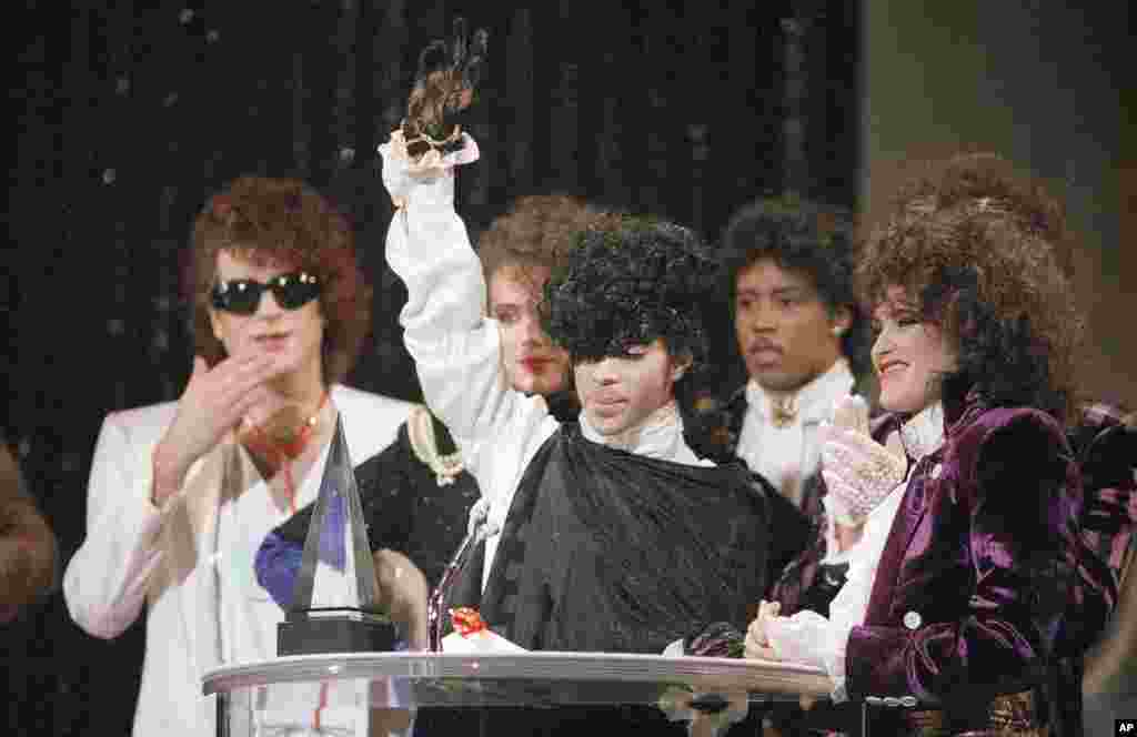 """Pop vocalist Prince holds up a hand as he accepts an American Music Award for his single """"When Doves Cry"""" during presentations at the Shrine Auditorium in Los Angeles, Jan. 28, 1985."""