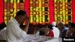 8일 중국 상하이 증권시장에서 투자가들이 전광판을 쳐다보고 있다.
