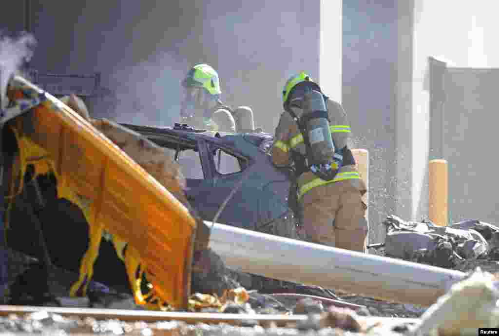 Emergency services personnel are seen at the site of a plane crash in Essendon, in Melbourne, Australia.