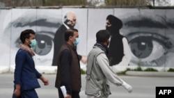 Orang-orang mengenakan masker untuk mencegah penularan Covid-19 melintasi dinding yang dilukis gambar Utusan Khusus AS untuk Rekonsiliasi Afghanistan Zalmay Khalizad (kiri) dan salah satu pendiri Taliban, Mullah Abdul Ghani Baradar (kanan), di Kabul, Afghanistan, 5 April 2020.