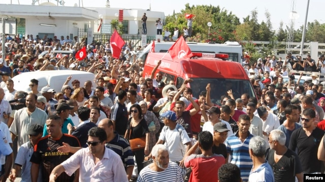 People walk beside the ambulance carrying the body of assassinated Tunisian opposition politician Mohamed Brahmi in Tunis, July 25, 2013.