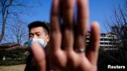 资料照片:中国安全人员阻挡新闻摄影师拍摄世界卫生组织一个专家组在武汉的行踪。(2021年2月6日)
