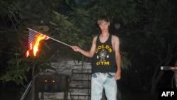 Bức ảnh không rõ ngày tháng được lấy từ trang web Lastrhodesian.com hôm 20/6/2015, cho thấy Dylann Roof đang đốt một lá cờ Mỹ. Trang web này không còn hoạt động.