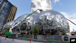 FILE - In this April 27, 2017 file photo, construction continues on three large, glass-covered domes as part of an expansion of the Amazon.com campus in downtown Seattle. Amazon is looking for the location of its second home base.