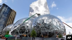 FILE - In this April 27, 2017 file photo, construction continues on three large, glass-covered domes as part of an expansion of the Amazon.com campus in downtown Seattle.