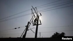 A technician is silhouetted as he works on power lines supplying electricity in the outskirts of Lahore, Pakistan, Jan. 31, 2012.