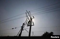 Silhouette seorang teknisi yang bekerja di jaringan listrik yang memasok listrik di pinggiran kota Lahore, Pakistan