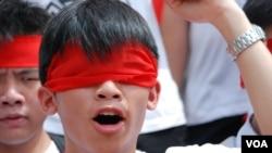 學民思潮成員黎汶洛以紅色紗布蒙眼,喻意學生拒絕被染紅洗腦國民教育蒙蔽 (美國之音湯惠芸)