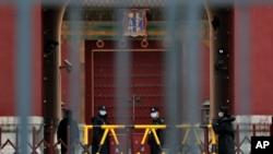 សន្តិសុខដែលមានពាក់ម៉ាស់ឈរយាមនៅខ្លោងទ្វារនៃវិមាន Forbidden City នៅក្នុងក្រុងប៉េកាំង កាលពីថ្ងៃទី១៩ ខែមេសា ឆ្នាំ២០២០។
