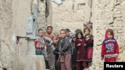 FILE - Internally displaced Afghan children are seen next to their shelters on the outskirts of Kabul, Feb. 3, 2021.