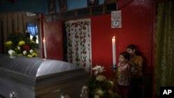 Dos de los seis hijas del periodista asesinado Julio Valdivia de pie junto a su ataúd durante un velorio en su casa ubicada en Tezonapa, Veracruz, en México. 10 de septiembre de 2020.