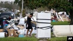 Seorang warga bernama Lori Butler tampak menyeka keningnya saat ia berusaha memindahkan puing puing dari rumahnya yang terendam banjir akibat diterjang badai Ida di LaPlace, Louisiana, AS, pada 7 September 2021. (Foto: AP)