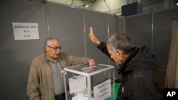 A Algerian voter casts his vote, Thursday, Dec.12, 2019, at the Algerian consulate in Marseille, southern France.