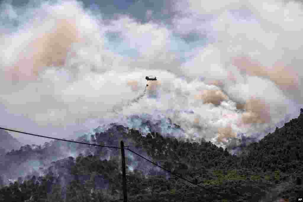 یک هلیکوپتر نظامی در حال پاشیدن آب بر روی آتش در جنگل در غرب آتن، یونان