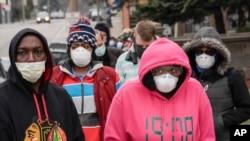 Arhiva - Glasači sa maskama na licu zbog koronavirusa, dolaze u Riversajd visoku školu kako bi glasali na preliminarnim izborima, 7. avgusta 2020. u Milvokiju.