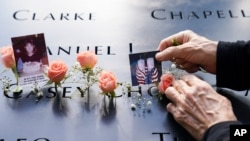 Mourners place flowers and pictures in the name cutout of Kyung Hee (Casey) Cho at the National September 11 Memorial and Museum, Sept. 11, 2020, in New York.