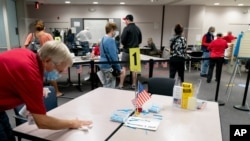 A poll worker wipes down a table as people wait over four hours for early voting at Fairfax County Government Center, Sept. 18, 2020, in Fairfax, Virginia.