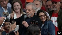 El expresidente de Brasil Luiz Inacio Lula da Silva habla a simpatizantes junto a su novia Rosangela da Silva eans on his back after he was released from Federal Police headquarters where he was imprisoned on corruption charges in Curitiba, Brazil,…
