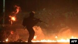 Un soldado israelí pasa frente a unas llantas quemadas en protesta en la Franja de Gaza.
