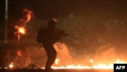 Seorang petugas keamanan Israel melewati ban-ban yang dibakar dalam demonstrasi sekitar 10.000 warga Palestina yang memprotes serangan militer Israel di Gaza, di antara Yerusalem dan Ramallah (25/7). (AFP/Abbas Momani)