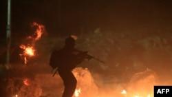 一名以色列士兵,背景是燃烧的轮胎。一万多巴勒斯坦人游行抗议以色列对加沙的军事袭击,在过境点检查站和以防军人及边境警察发生冲突。