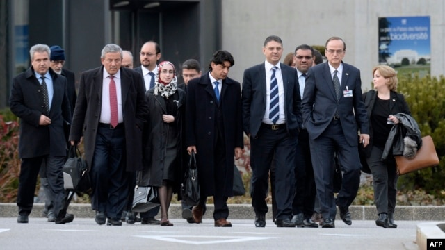 "Syrian opposition chief negotiator Hadi al-Bahra (2nd R) and General Secretary of the Syrian National Council Badr Jamous (4ht R) arrive with the opposition delegation to attend a meeting at the ""Geneva II"" peace talks dedicated to the ongoing conflict in in Syria, in Geneva, Jan. 25, 2014."