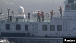Crew members onboard a Chinese coast guard vessel are pictured on the South China Sea,