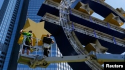 FILE - Workers dismantle the large euro sign sculpture for maintenance, in front of the headquarters of the former European Central Bank (ECB) in Frankfurt, July 6, 2015.
