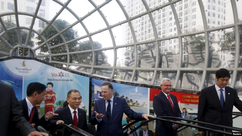 Chủ tịch Vingroup Phạm Nhật Vượng (thứ hai từ trái sang) đón Thủ tướng New Zealand John Key sau khi ông đến thăm một cửa hang Vinmart ở Hà Nội hồi năm 2015