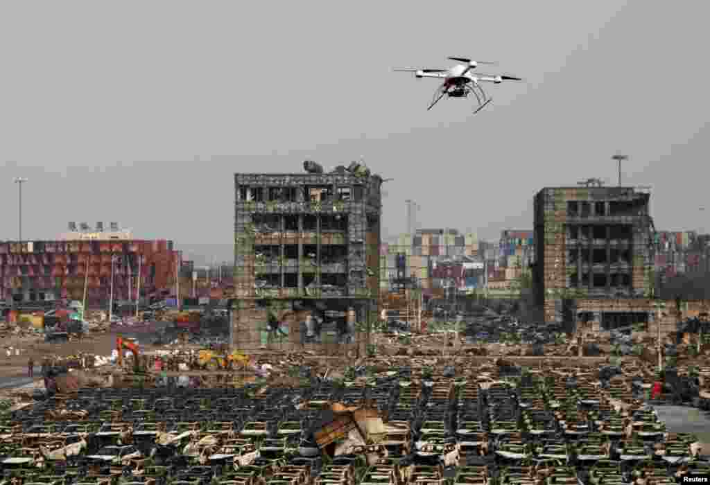 A drone operated by paramilitary police flies over the site of last week's explosions at Binhai new district in Tianjin, China. Many operations have resumed at China's Tianjin port, trade sources said, after explosions last week that killed more than 100 people and disrupted business at what is an important oil, gas and bulk import harbor for Asia's biggest economy.