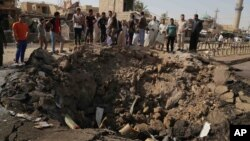 FILE - Civilians inspect a crater caused by a suicide car bombing at a busy market in Khan Bani Saad in the Diyala province, about 30 kilomters (20 miles) northeast of Baghdad, Iraq, July 18, 2015.