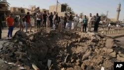 Người dân đứng nhìn một cái hố lớn xuất hiện sau vụ đánh bom xe tự sát tại một khu chợ đông đúc ở Khan Bani Saad thuộc tỉnh Diyala, cách Baghdad 30 km về phía đông bắc hôm 18/7.