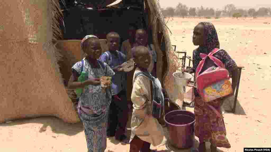 Des enfants avec leurs repas devant l'école à Bosso dans la région de Diffa, Niger, le 19 avril 2017 (VOA/Nicolas Pinault)