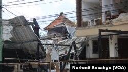 Sejumlah pekerja membersihkan bagian hotel yang rusak parah di kawasan wisata Senggigi, Lombok, 9 Agustus 2018. (Foto: Nurhadi Sucahyo)