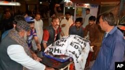 Volunteers carry the body of a shooting attack victim, at a hospital in Quetta, Pakistan, April 2, 2018.
