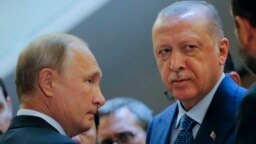 Russian President Vladimir Putin (L) and Turkish President Recep Tayyip Erdogan prepare to enter a hall for their talks at the Bocharov Ruchei residence, in Sochi, Russia, Sept. 17, 2018.