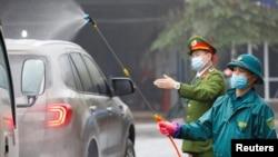 越南防疫官员为防范新冠病毒疫情给车辆喷洒消毒药水。(2020年2月7日)