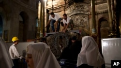 FILE - Christian nuns watch as experts begin renovation of Jesus' tomb in the Church of the Holy Sepulchre in Jerusalem's old city, June 6, 2016. The team has begun a historic renovation at the spot where Christians believe Jesus was buried, overcoming longstanding religious rivalries to carry out the first repairs in more than 200 years.
