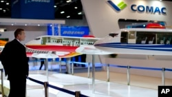 Seorang pengunjung mengamati sebuah model pesawat jet komersial pertama China, ARJ21 di sebuah pameran dirgantara di Beijing, Rabu (25/9).