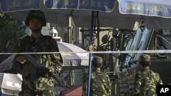 ກຳລັງຮັກສາຄວາມສະຫງົບ ຕິດອາວຸດຄົນນຶ່ງຂອງຈີນ ຢືນຍາມທີ່ແຄມຖະໜົນແຫ່ງນຶ່ງ ໃນເມືອງ Kashgar ໃນເຂດຊີນຈຽງຂອງຈີນ (30 ມັງກອນ 2012)