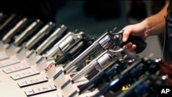 FILE - Handguns are displayed at the Smith & Wesson booth at the Shooting, Hunting and Outdoor Trade Show in Las Vegas, Jan. 19, 2016.