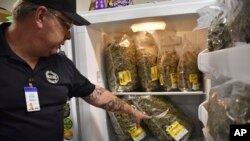 Montana Advanced Caregivers owner Richard Abromeit talks about different strains of marijuana stored in a refrigerator at the Billings, Mont., medical marijuana dispensary on Nov. 11, 2020. (AP Photo/Matthew Brown)
