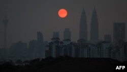 A general view shows Malaysia's landmark Petronas Twin Towers (2nd R) and Kuala Lumpur Tower (L) as a layer of haze covers the city during sunset in Kuala Lumpur, March 30, 2016.
