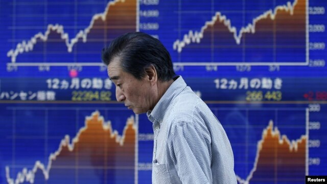 A man walks past a stock quotation board outside a brokerage in Tokyo, June 3, 2013.